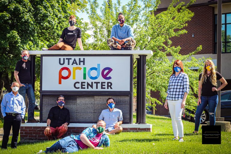 Group image of the Staff of our Community Counseling Center. They are standing or sitting next to, in front of, and on top of the Utah Pride Center Street-level sign.
