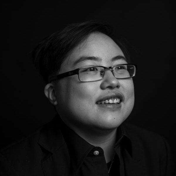 [Photo: Black and white image of Lydia X. Z. Brown, a young East Asian person with glasses, smiling and laughing, looking slightly away from the camera. Photo by Colin Pieters.
