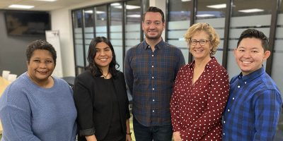 Photo of Utah Pride Center Executive Board. From left to right: Tanya Hawkins (she-her-hers), Gloria Castaneda (she-her-hers), Chris Jensen (he-him-his), Chris Decaria (she-her-hers), and Michael Iwasaki (he-him-his).