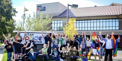 Utah Pride Center Team gathered outside on the lawn in front of the UPC Sign with the building in the background. Everyone has their hands up as if waving. Everyone is wearing a mask for COVID-19.